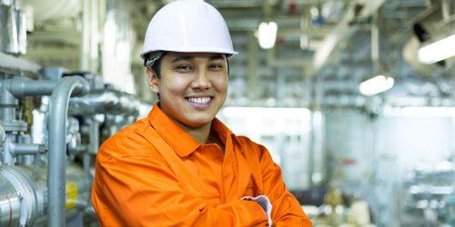 67605700 - smiling asian engineer in white helmet in industrial space.